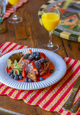 White plate with french toast strawberries,blueberries and huckleberries. Water and Orange juice on side