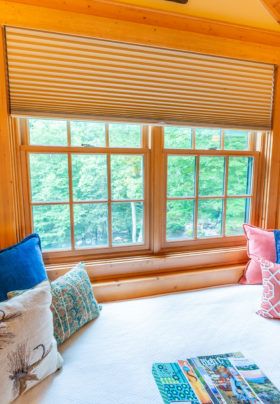 Window bed in Cascades room. View of the River and trees outside. White bedspread with colorful pillows and magazines on top.