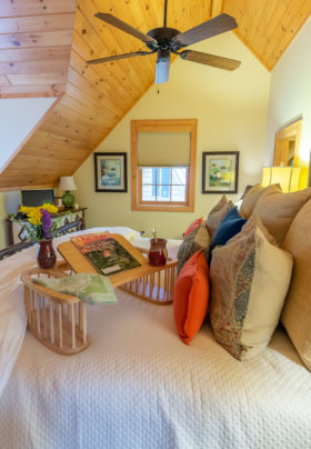 side view of Cascades room. King sized bed with pillows. Breakfast table with flowers, napkin, magazines and coffee on top. View of the window bed w/ pillows and magazines on top. View of the trees outside