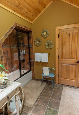 bathroom off of Cascades. Dressing table ... Bath and shower combination across from wooden vanity, hair dryer on wall