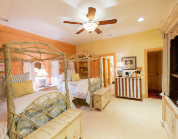 Hummingbird room...white painted branch beds with canopies Yellow and blue spreads with white comforters on end of bed. Trunks are sitting in front of each bed. Low chest sitting between beds with lamp. white and cherry striped chest on wall with lamp and coffee maker, ice bucket and tray next to door. White chest with tv on wall across from beds. Looks into the bathroom and hallway from this view