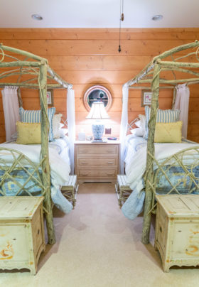 Hummingbird room...white painted branch beds with canopies Yellow and blue spreads with white comforters on end of bed. Trunks are sitting in front of each bed. Low chest sitting between beds with lamp
