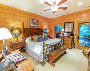 Rainbow Trout bedroom -log walls w/ wooden headboard and footboard. Bench painted with trout sits at the foot of the bed. Two bedside tables w/ chest on side wall. Rocking chair is in corner by the door which leads to the outside.