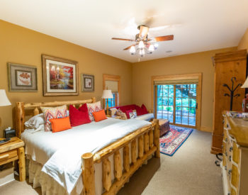 King sized wooden bed with white bedding. Six pillow are on bed. Two bed side tables with lamps are on each side of bed. Futon located on right hand side of bed in front of window and sliding door. Rug is in front of futon with chest on top. Dresser in front of bed and wardrobe is next to dresser.