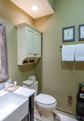 Bathroom off of Mountain Laurel... sink/ with wooden mirror. Cabinet over toilet. Green Wall with 2 towels on towel bar and bear holding toilet paper. Stones on surround of shower located on the right hand side of room