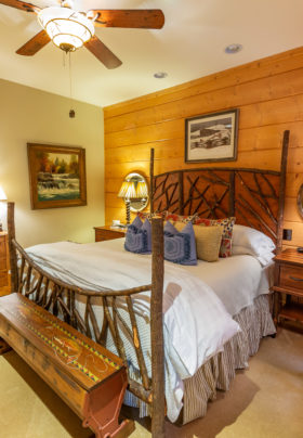 Rainbow Trout bedroom -log walls w/ wooden headboard and footboard. Bench painted with trout sits at the foot of the bed. Two bedside tables w/ chest on side wall.