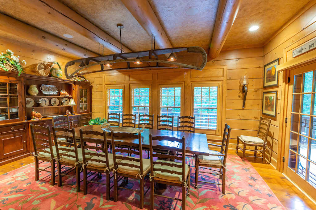 Dining room large tables with 12 ladder back chairs sitting on red rug with leaves. Canoe light fixture over table. China cabinet on side wall. Outside is seen through the 4 windows and doors.