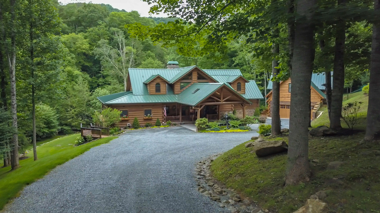 The Lodge at River Run picture as you come down driveway to house. Log House w/green tin roof surrounded by trees and flower beds