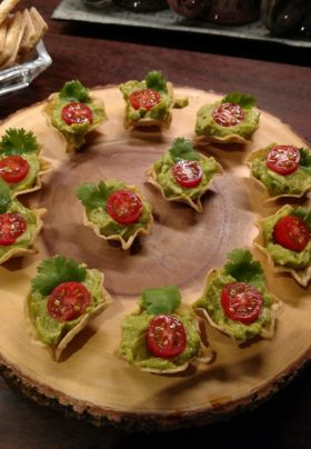 round of wood platter with tortilla scoops filled with guacamole and cherry tomatoes and a spring of cilantro. another dish with pimento cheese and assorted crackers