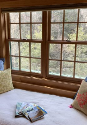 Window day bed looking over the Elk River. Pillows on the bed with monthly assorted magazines. Antler Sconces are on both walls encasing the bed