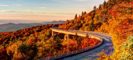 View of the Blue Ridge parkway. Vibrant colors are on the trees.. green, ted, orange, yellow. Mountains seem to go on for miles..