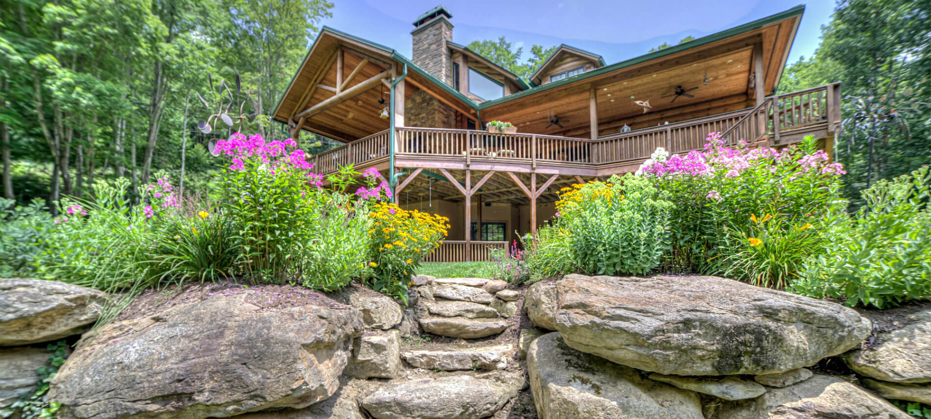 Back view of the Lodge. Large rock wall with rock steps lead up to the house. There are two beds of colorful flowers on both sides of steps. Yellow, orange and purple flowers are in beds.