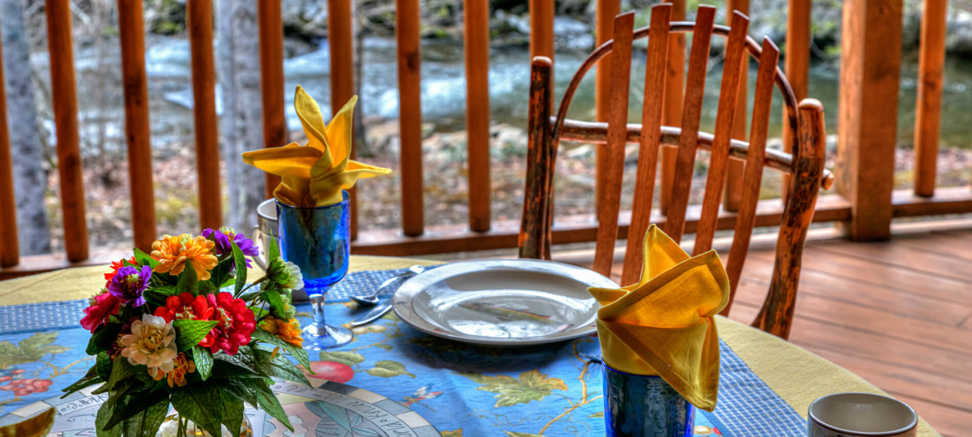 Table outside on porch. French flowers in the center of table. Fish plates with blue glasses and gold napkins . Background is the river that runs by.