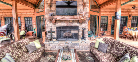 Outside porch with stone fireplace. TV is over the mantel. Two sofas and coffee table are in front of sofas. Two chairs with ottomans are back of sofa on left and table set for breakfast is behind the sofa on the right.