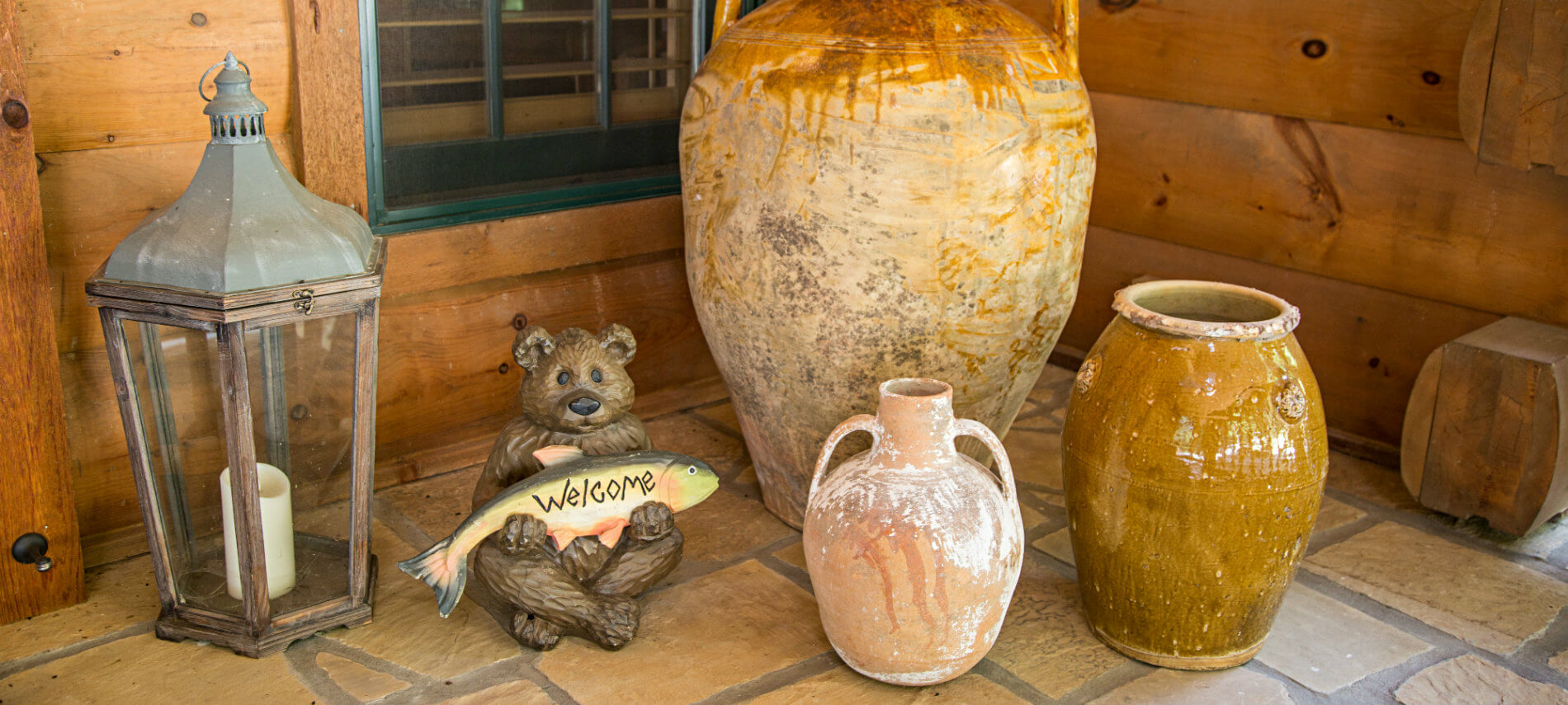 Different sized clay pots on porch. Wooden bear that is holding a trout which says Welcome on it is sitting by pots. A lantern with candle sits by the door