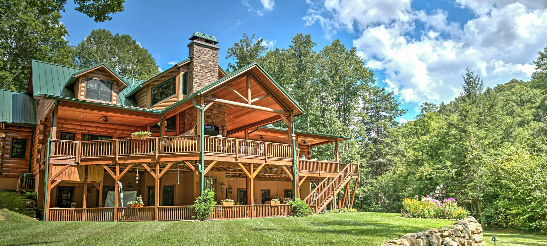 View of the Lodge showing two porches with window boxes on railing. Trees and flowers surround the house.