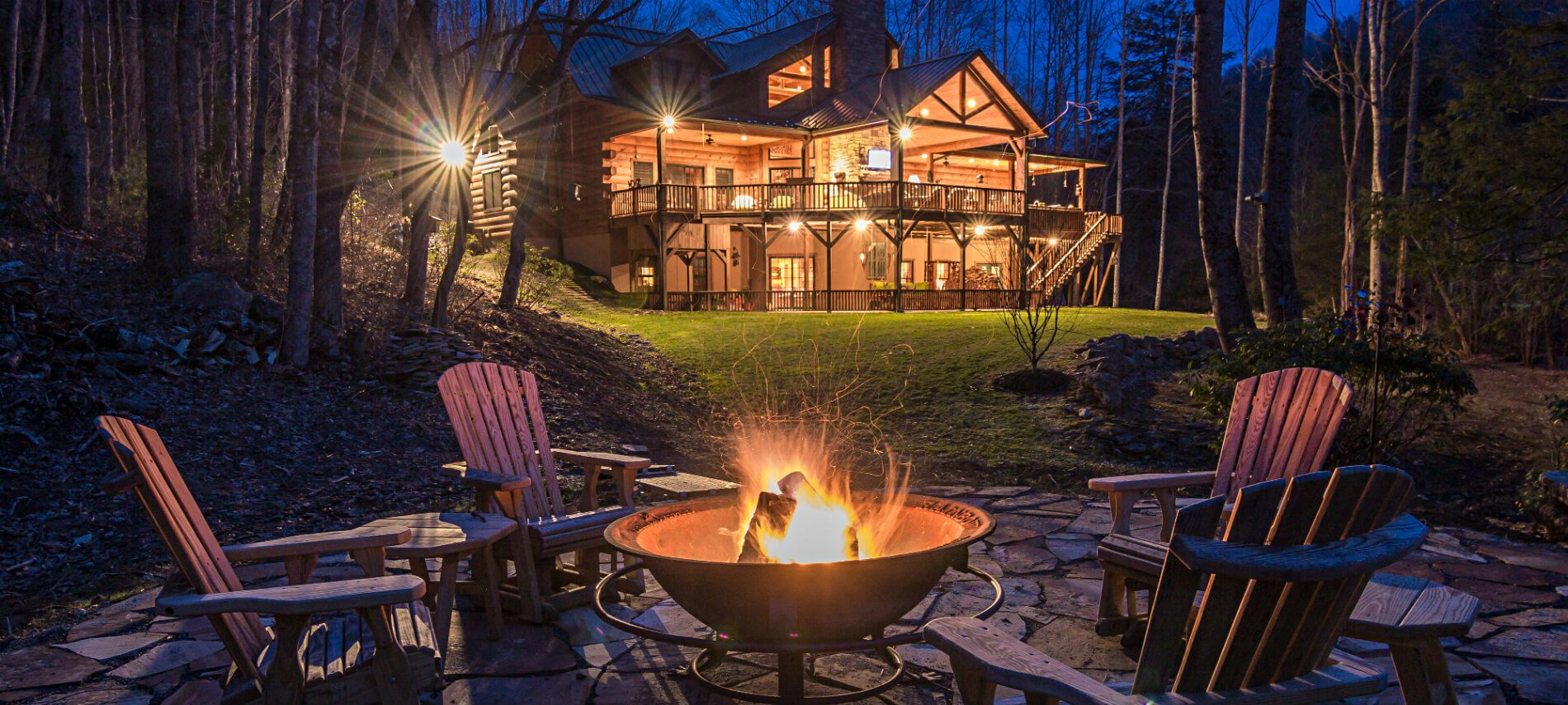 The Lodge at River Run view at night. The fire is in the fire pit which is surrounded by four chairs.Tree surround the sides of the house.