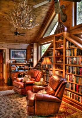 Library with 2 leather recliners sitting on rug. Books line the shelves . There is large antler chandelier over the chairs.