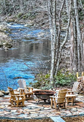 Fire pit is sitting on round stone patio with four rocking chairs. It is surrounded by trees that and above the river that flows by
