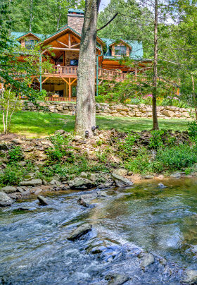 view from back of lodge surrounded by stone wall. The river is shown with the rocks and trees in back of the house.