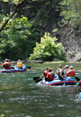 two boats with people paddling as they are white water rafting down river.
