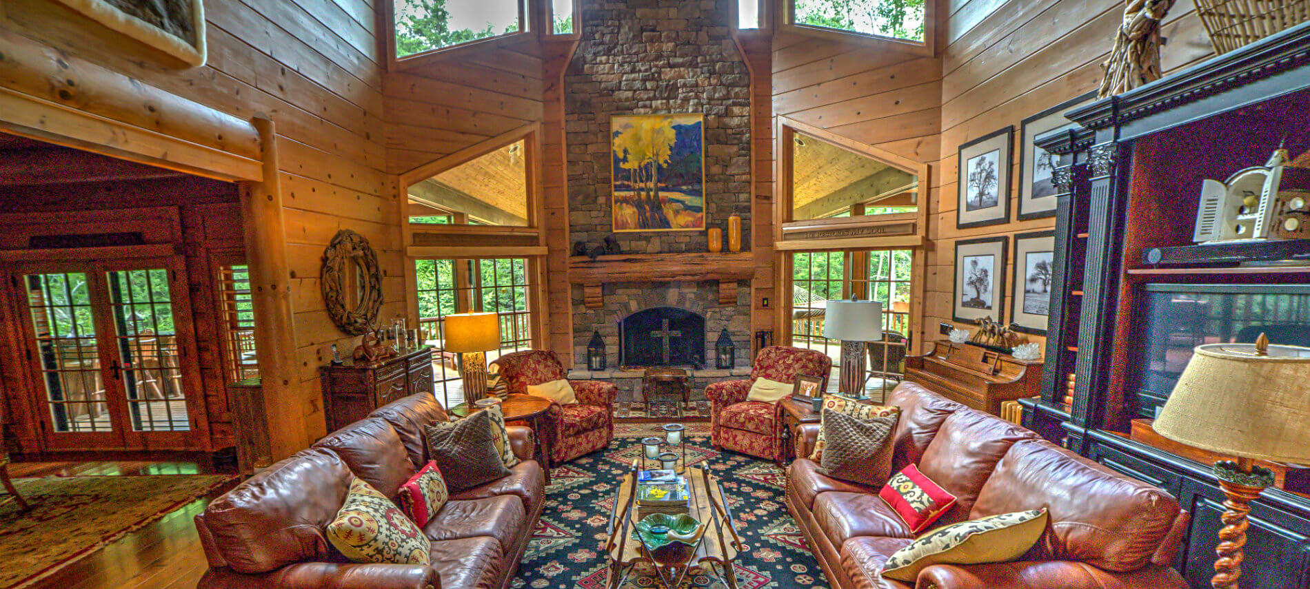 Large family room with 2 leather sofas and 2 fabric recliners. Stone fireplace with large painting over the top of mantel. Piano on the side wall which has black and white pictures of trees. TV is behind one of the sofas. The kitchen is seen from the family room. There are views of the outside from the 2 double doors in family room and 1 in the kitchen