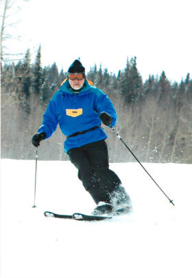 Man skiing down mountain. Trees are in background
