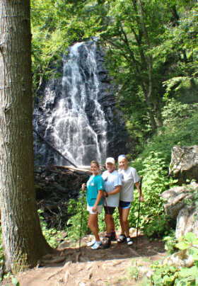 Three ladies standing in front of waterfall. Surrounded by rock and trees
