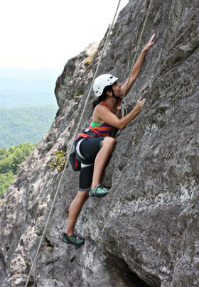 Lady is rock climbing in the mountains.